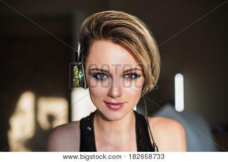 Lovely joyful girl with tanned skin and white hair listening to music on headphones. Female beauty joyful portrait of a beautiful makeup. Enjoying good music. Joyful model