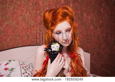 Woman with long red curly hair in a braid and a doll in hands in nightgown in bed under a blanket. Red-haired girl with pretty face pale skin blue eyes and bright unusual appearance in the bedroom