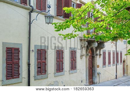 Street lamps and closed shutters in a quiet street - Arezzo, Italy