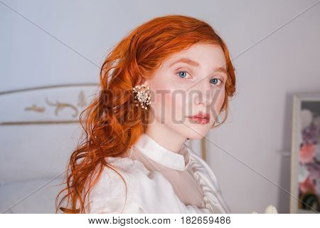Portrait of a woman with long red curly hair in a white vintage wedding dress with white pearl earrings on her ears looking camera. Red-haired girl with a pale skin blue eyes a bright unusual appearance in bedroom looking camera. Model looking in camera.