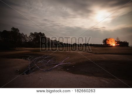 Man blazing fire. The beautiful night scenery. Slow shutter speed. Spectacular clear starry sky. Scenic view. The light from the fire on the trees