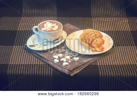 Croissant with chocolate spread and butter cup of coffee