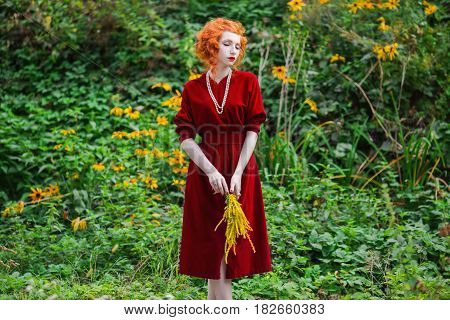A woman with red hair and a red slinky dress with a bouquet of yellow flowers in hand. Red-haired girl with pale skin blue eyes and bright unusual appearance with a necklace of beads around her neck