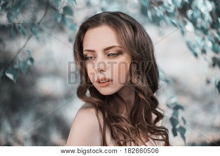 Beauty portrait of a very pretty young girl. Doll appearance. Pretty woman with brown hair in a pink wedding dress on nature. Long hair pretty woman. Natural light. Pretty model