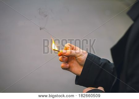 Lucifer match with fire in hands action