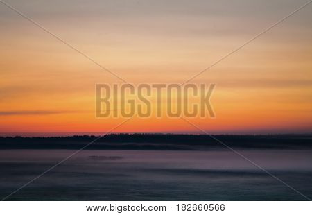 It begins a new day on horizon. The orange morning sky under horizon. Fog over the valley horizon. Mystical landscape with horizon. Water surface. Trees in the field on horizon. The gloomy picture