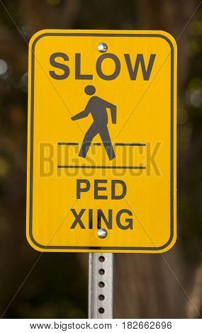 Slow pedestrian crossing yellow sign vertical shot.