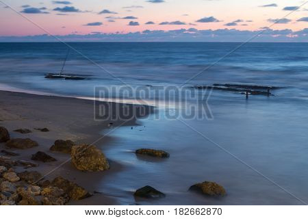 Stones fishing rods beautiful sea and sky after sunset