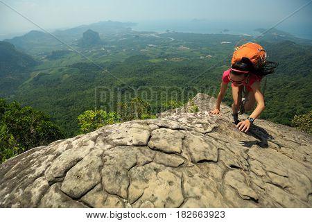 young woman climber climbing rock at mountain top