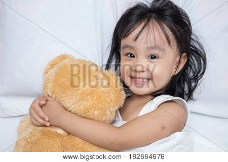 Asian Little Chinese Girl Hugging A Teddy Bear