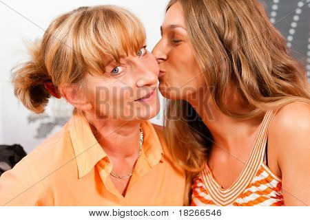 Daughter is kissing her mother as a sign of love