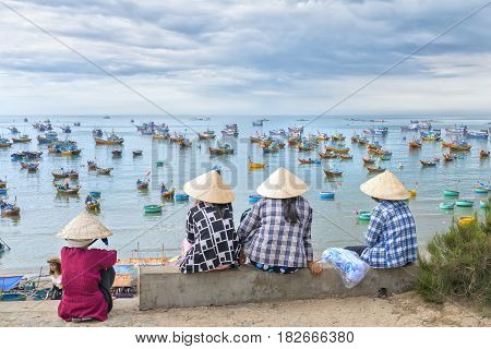 Mui Ne, Vietnam - February 19th, 2017: A group of vietnamese women waiting for the fishing boat on the port in a small village close to Mui Ne, Vietnam.