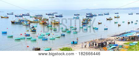 Mui Ne, Vietnam - February 19th, 2017: Fishing village and traditional Vietnamese fishing boats with hundreds of boats moored in a line beautifully. This is the bay for boat storm in central Vietnam