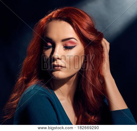 Portrait of beautiful young woman with red hair and bright makeup