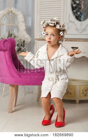 Little girl fashionista. A girl in curlers a robe and red high-heeled shoes. Little coquette. She is very surprised.