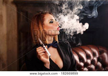 Young attractive girl in a jacket and bow tie smokes electronic cigarette. Femme fatale. Evening makeup smokey eye. She lets out a thick steam from her mouth