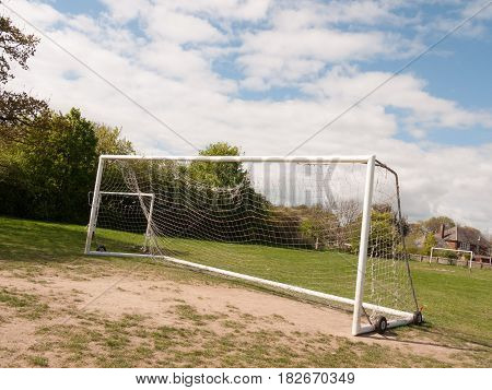 An Empty And Unused Goal Post With A White Net In The Middle Of A Park With Grass And Soil On The Gr