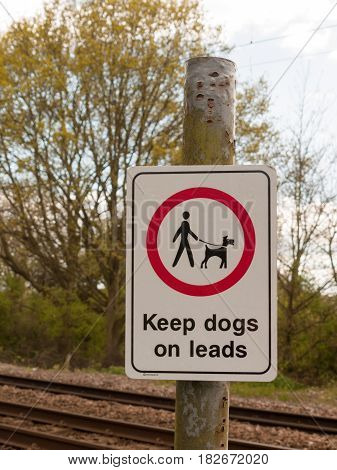 A Railway Safety Sign Saying Keep Dogs On Leads In White And Red And Black On A Pole With Background