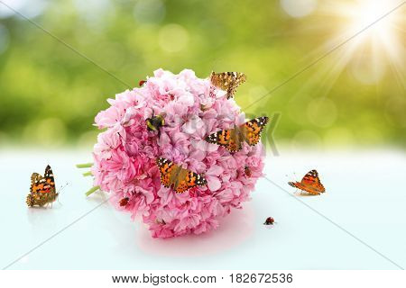A wedding bouquet with insects. Butterfly, bee, bumblebee, ladybug crawling on the flowers in the sun.
