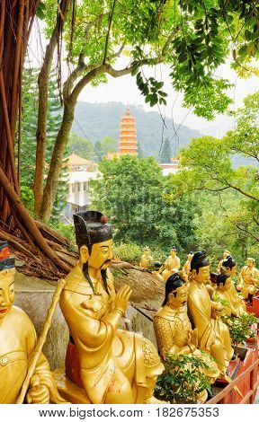 Golden Buddha Statues On Background Of A Red Pagoda And Landscape In Hong Kong