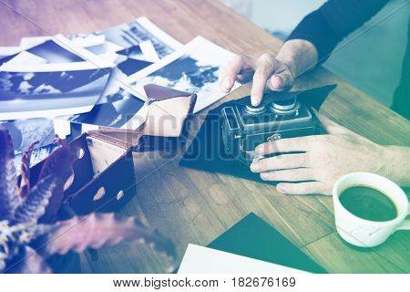 photographer hands cleaning camera lens on wooden table
