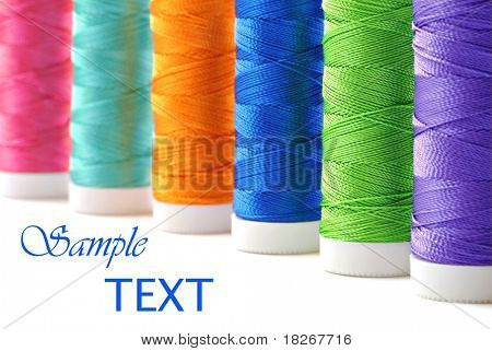 Colorful spools of thread on white background with copy space.  Macro with shallow dof.  Selective focus on green thread.