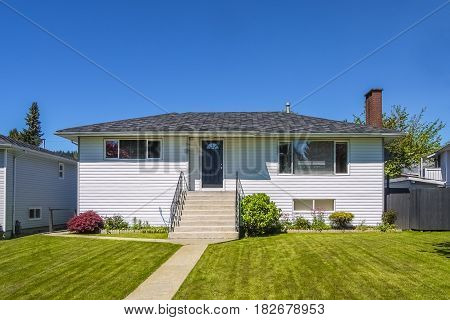 Old modest residential house with concrete pathway over front yard lawn. Family house with freshly mowed lawn