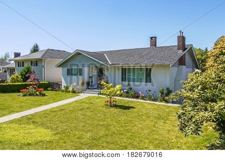 Average family house with concrete pathway over front yard. Residential house on sunny day on blue sky background