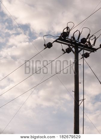 An Overhead Electrical Wire Post With Metal Wires Running To And From With A Cloudy Background Isola