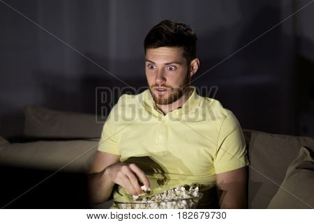 people, mass media, television and entertainment concept - scared young man watching tv and eating popcorn at night at home