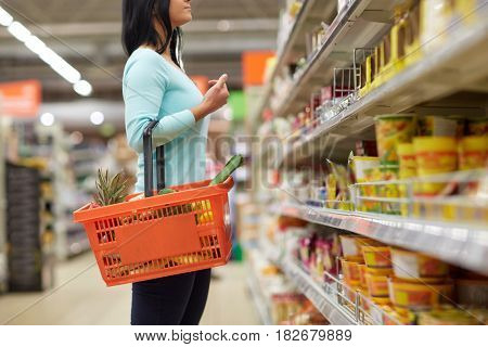 sale, shopping, consumerism and people concept - woman with food basket at grocery store or supermarket