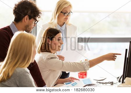 business, startup and people concept - happy creative team networking with computer in office