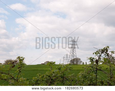 A Shot Of Far Away Field Green And With Several Lined Up Electrical Wire Metal Frames Standing And W