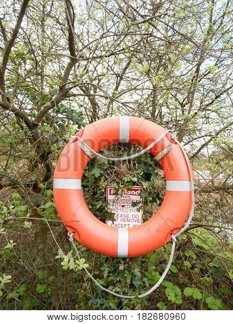 An Orange And Silver Life Buoy With Rope With A Safety Sign Behind It In The Forest Next To A Lake