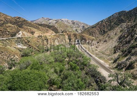 Road And Railroad Track In Desert