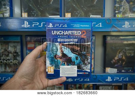Bratislava, Slovakia, circa april 2017: Man holding Uncharted 2 Among thieves videogame on Sony Playstation 4 console in store