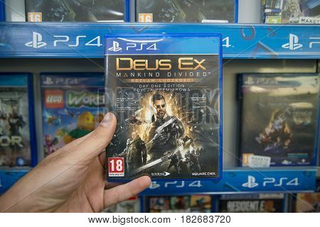 Bratislava, Slovakia, circa april 2017: Man holding Deus Ex Mankind Divided videogame on Sony Playstation 4 console in store