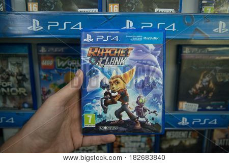 Bratislava, Slovakia, circa april 2017: Man holding Ratchet and Clank videogame on Sony Playstation 4 console in store