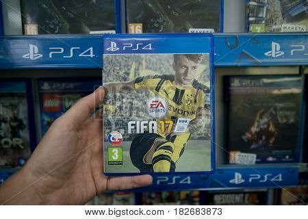 Bratislava, Slovakia, circa april 2017: Man holding Fifa 17 videogame on Sony Playstation 4 console in store