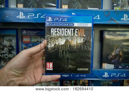 Bratislava, Slovakia, circa april 2017: Man holding Resident Evil 7 videogame on Sony Playstation 4 console in store