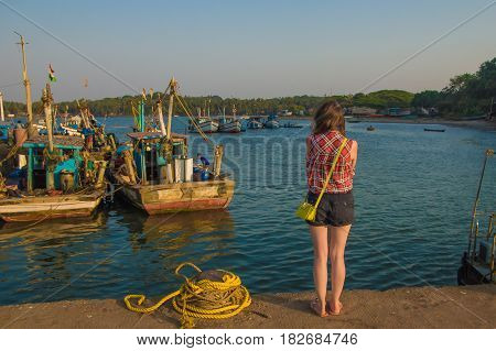 Fishing Boats In Chapora Port In Goa, India. Young Woman On The Berth
