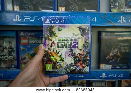 Bratislava, Slovakia, circa april 2017: Man holding Plants vs Zombies Garden Warfare 2 videogame on Sony Playstation 4 console in store