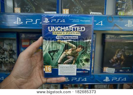 Bratislava, Slovakia, circa april 2017: Man holding Uncharted Drake's Fortune remastered videogame on Sony Playstation 4 console in store