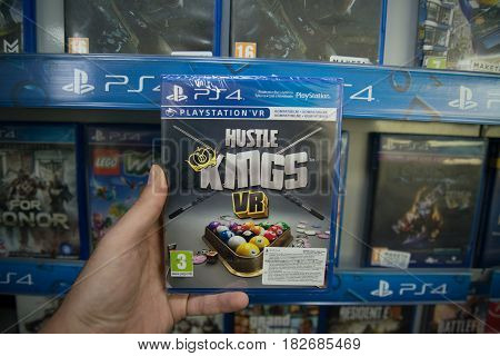 Bratislava, Slovakia, circa april 2017: Man holding Hustle Kings VR videogame on Sony Playstation 4 console in store