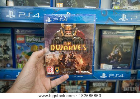 Bratislava, Slovakia, circa april 2017: Man holding The Dwarves videogame on Sony Playstation 4 console in store