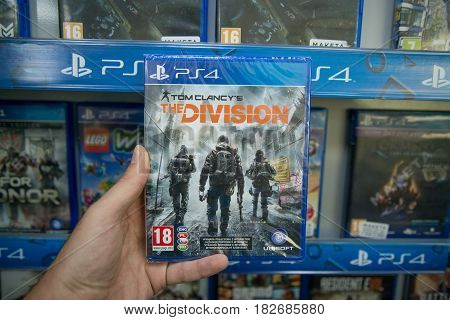 Bratislava, Slovakia, circa april 2017: Man holding Tom Clancy's The Division videogame on Sony Playstation 4 console in store