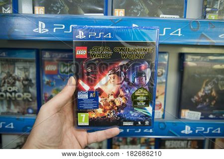 Bratislava, Slovakia, circa april 2017: Man holding Lego Star Wars Force Awakens videogame on Sony Playstation 4 console in store