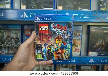 Bratislava, Slovakia, circa april 2017: Man holding Lego Movie videogame on Sony Playstation 4 console in store