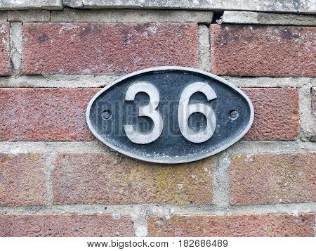 A Number Plate On A Brick Wall With 36 On It