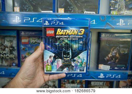 Bratislava, Slovakia, circa april 2017: Man holding Lego Batman 3 videogame on Sony Playstation 4 console in store